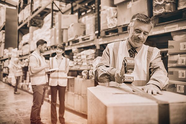 Man packing shipping boxes full of paper and toner while two other men discuss order